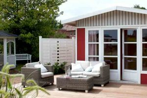 Beispiel einer richtigen Holzpflege: Holzhaus mit Terrasse in Naturöl-Farben